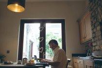 Senior man using digital tablet on dining tablet at home — Stock Photo