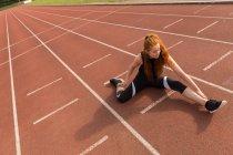 Giovane atletica femminile che esercita sulla pista da corsa — Foto stock