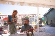 Жіночий офіціантка, приймаючи замовлення в придорожньому кафе сонячний день — стокове фото