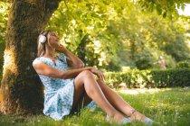 Женщина слушает музыку против дерева в парке — стоковое фото