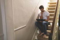 Young man using laptop on staircase at home — Stock Photo