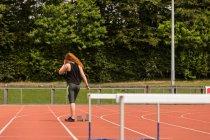Vista posteriore dell'atleta donna in piedi sulla pista da corsa — Foto stock