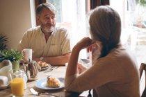 Couple de personnes âgées interagissant entre eux tout en prenant son petit déjeuner à la maison — Photo de stock
