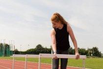 Joven atleta arreglando obstáculos en pista de atletismo - foto de stock