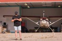 Механик, с помощью мобильного телефона в аэрокосмической ангар — стоковое фото