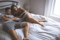 Пара, використовуючи ноутбук у спальні будинку — стокове фото
