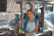 Female waitress holding vegetables in basket near food truck — Stock Photo