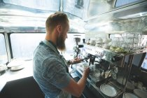 Side view of waiter preparing coffee in food truck — Stock Photo