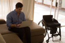 Disabled man using laptop in living room at home — Stock Photo
