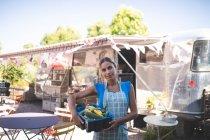 Официантка держит овощи в корзине рядом с фургоном — стоковое фото