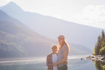 Couple standing near riverside in mountains — Stock Photo