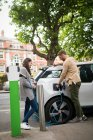 Couple charging electric car at charging station — Stock Photo