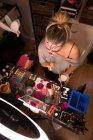 Mujer pintando su cara con pincel para la celebración de Halloween - foto de stock