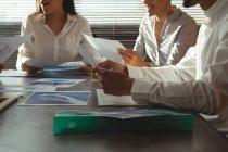 Section médiane des cadres discuter par rapport au document dans la salle de conférence au bureau — Photo de stock