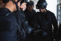 Военные обсуждают свой план за цифровым планшетом во время военной подготовки — стоковое фото