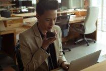 Executive che utilizza il computer portatile mentre parla sul telefono cellulare in ufficio — Foto stock