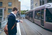 Homme d'affaires contrôle temps dans son smartwatch à la gare — Photo de stock