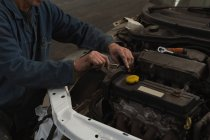 Mid section of male mechanic servicing a car in garage — Stock Photo