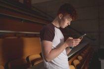 Vista lateral del estudiante universitario usando tableta digital en el aula - foto de stock