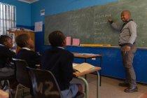 Professora do sexo masculino ensinando alunos na turma na escola — Fotografia de Stock