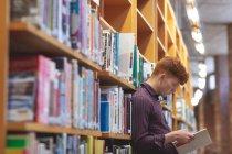 Seitenansicht des College-Studenten, die ein Buch in der Bibliothek — Stockfoto