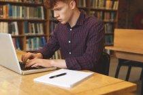 Estudiante universitario atento usando el ordenador portátil en la biblioteca - foto de stock