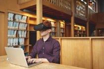 Студент колледжа с помощью ноутбука и гарнитуры виртуальной реальности в библиотеке — стоковое фото