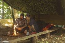 Pareja joven relajándose en el campamento - foto de stock