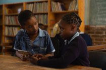 Schoolkids using digital tablet in classroom at school — Stock Photo