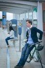 Вид сбоку бизнесмена, прислонившегося к велосипеду на вокзале — стоковое фото