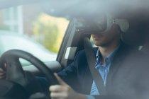 Homme d'affaires intelligent à l'aide de casque de réalité virtuelle pendant que vous conduisez la voiture — Photo de stock
