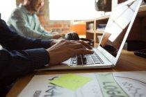 Vista lateral del ejecutivo utilizando el ordenador portátil en el escritorio en la oficina - foto de stock