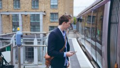 Young businessman using mobile phone at railway station — Stock Photo