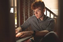 Студент колледжа использует ноутбук на лестнице в кампусе — стоковое фото