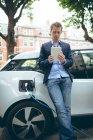 Uomo d'affari che utilizza tablet digitale durante la ricarica di auto elettriche presso la stazione di ricarica — Foto stock