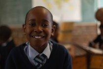 Школьник, стоя в классе в школе — стоковое фото