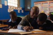 Insegnante di sesso maschile che insegna agli studenti in classe a scuola — Foto stock