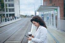 Деловая женщина с чашкой кофе с помощью мобильного телефона на железнодорожной станции — стоковое фото