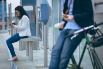 Young businesswoman using mobile phone at railway station — Stock Photo
