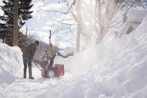 Man using snow blower machine in snowy region during winter — Stock Photo