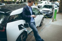 Businessman using mobile phone while charging electric car at charging station — Stock Photo