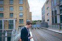 Jeune homme d'affaires à l'aide de téléphone portable à la gare — Photo de stock