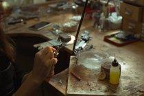 Jewelry designer holding wielding torch in workshop — Stock Photo