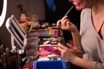 Жінка живопис її обличчя з щіткою для святкування Хеллоуїна — стокове фото