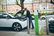 Young businessman charging electric car at charging station — Stock Photo