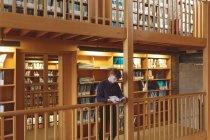 Студент коледжу уважний, читаючи книгу в бібліотеці — стокове фото