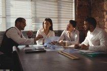 Cadres supérieurs discutant par rapport au document dans la salle de conférence au bureau — Photo de stock