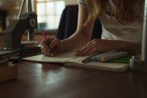 Средний раздел ювелирного дизайнера написание на регистре в мастерской — стоковое фото