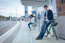 Homme d'affaires appuyé contre le vélo et utilisant le téléphone portable à la gare — Photo de stock