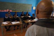 Männlicher Lehrer unterrichtet Schüler im Klassenzimmer in der Schule — Stockfoto